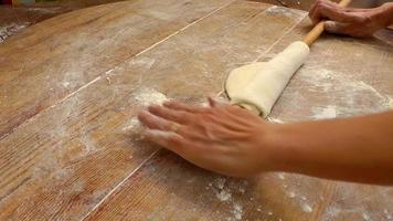 Abra a massa em uma mesa de madeira