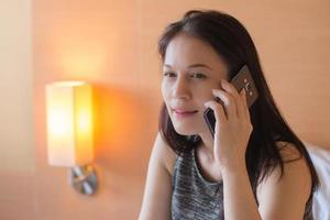 Business woman talking cell phone on bed in hotel room