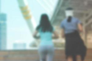 Mujer joven borrosa corriendo con un amigo o trotando en las calles de la ciudad foto
