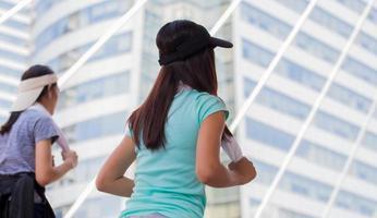 Hembra joven corriendo con un amigo o trotando en las calles de la ciudad foto