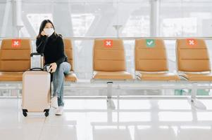 Woman wearing face mask sitting on social distancing chair with luggage