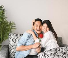Happy Asian couple hugging and enjoying a good time together photo