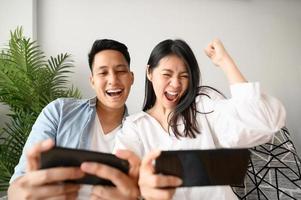 Couple having fun playing games on smartphone photo