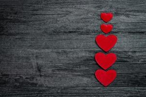 Red heart column on dark old wooden background photo