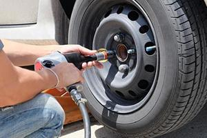 Man is changing a tire with wheel wrench photo