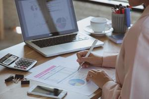 mujer de negocios joven que trabaja en la computadora portátil en la oficina foto