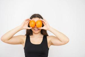 Beautiful young woman brunette holds oranges in front of her eyes photo