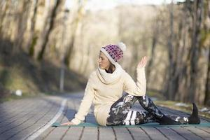 A young athletic woman performs yoga and meditation exercises outdoors photo