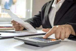 Businesswoman wearing a black suit and uses calculators at office photo