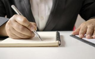 Close-up of a businesswoman using a pen to write photo