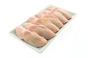 Alas de pollo crudas en la placa blanca. foto