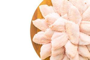 Alas de pollo crudo en placa de madera foto