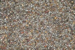 Mosaic of tiny gravel stones rock pieces stone wall texture photo