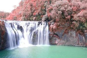 Waterfall near red autumn trees photo