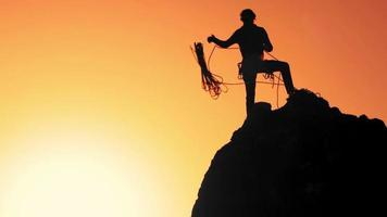 um alpinista no topo da rocha joga a corda em câmera lenta