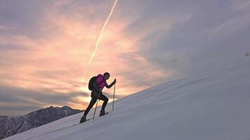 garota subindo com sapatos de neve durante um pôr do sol alpino video