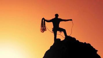 um alpinista no topo da rocha prepara a corda em câmera lenta