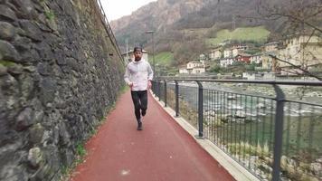 un hombre barbudo corre por un carril bici estrecho