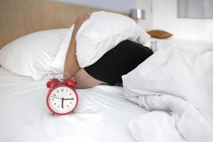 hombre siendo despertado por un reloj despertador foto