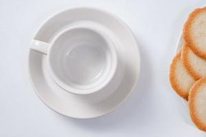 Taza de café con leche vacía con galletas sobre fondo blanco.