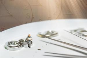 Miniature businessman sitting on a clock, concept of time and work