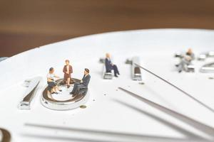 Miniature businesspeople sitting on a clock, concept of time and work