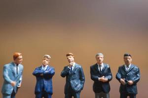 Empresarios en miniatura de pie sobre un fondo de madera, líder empresarial y concepto de trabajo en equipo foto