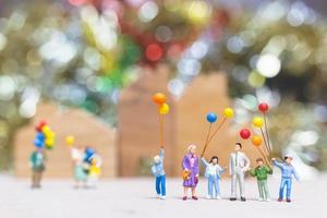 Miniature people holding balloons in a park with a colorful bokeh background, happy family relations and carefree leisure time concept photo