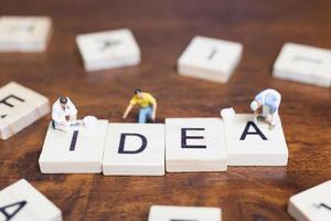 Miniature people standing with wooden blocks with the word Idea on a wooden background photo