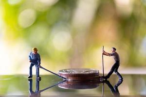 Miniature workers holding tools on coins with a green bokeh background, construction concept