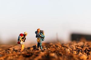 Miniature travelers with backpacks mountaineering, hiking and backpacking outdoors concept