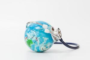 Stethoscope wrapped around a globe on a white background., save the world concept photo
