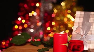 Geschenkbox und rote Kerze und buntes Bokeh im Hintergrund video
