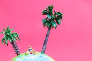 Miniature people wearing swimsuits relaxing on a globe with a pink background, honeymoon concept