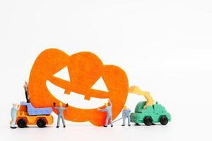 Trabajadores en miniatura que se unen para crear accesorios de fiesta de Halloween sobre un fondo blanco. foto