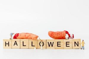 Miniature workers teaming up to create Halloween party props with wooden blocks with the text Halloween on a white background photo