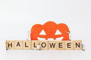 Trabajadores en miniatura que se unen para crear accesorios de fiesta de Halloween con bloques de madera con el texto Halloween sobre un fondo blanco. foto