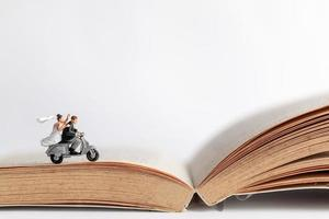 Miniature couple riding a motorcycle on an old book, Valentine's Day concept