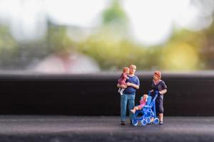 Miniature parents with children walking outdoors, happy family concept