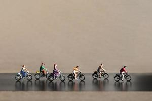 Miniature travelers riding bicycles, healthy lifestyle concept photo