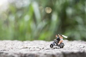 Miniature couple riding the a motorcycle on a blurred nature background photo