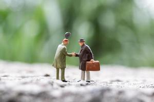 Miniature businesspeople shaking hands outdoors, connecting with people concept