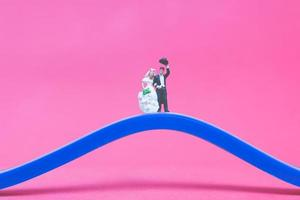 Miniature wedding, a bride and groom on a bridge on a pink background photo