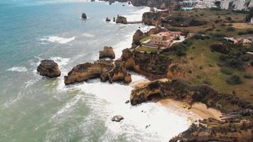 Rocky coastline, Praia dos Estudantes beach, Lagos, Algarve. Mansion on top of cliff. Aerial forward video