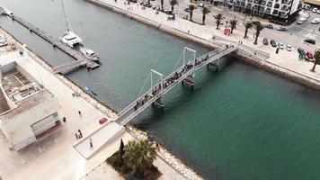 Crowd of people crossing a pedestrian bridge at Marina de Lagos, Algarve video