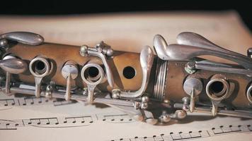 détail d'une vieille clarinette reposant sur une partition musicale. gros plan panoramique video