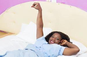 sonriente, mujer joven, con, mano extendida, mentira en cama foto