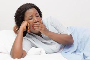 Young African woman yawns lying in bed at home photo