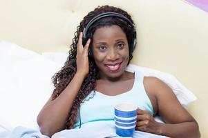 mujer joven se despierta con música y buen humor foto