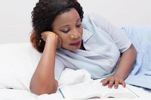 mujer joven, leer un libro, en cama foto